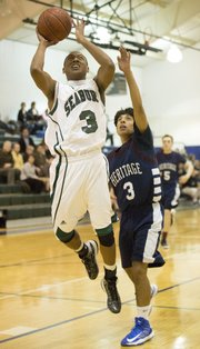 Seabury's Marcus Allen, left, soars past Thomas Tangari on his way to the basket during Bishop Seabury's game against Topeka Heritage, Tuesday, Feb. 5, 2013 in Lawrence.