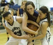 Bishop Seabury's Alexa Gaumer, left, and teammate Regan Zaremba, right, team up to take the ball away from Danielle McElory, center, during the Seahawks' game against Topeka Heritage, Tuesday, Feb. 5, 2013 at Seabury.