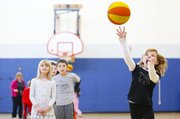 Second-grader Kira Kimmel heaves a shot at the bucket during a gym class dedicated to participation in the American Heart Association's Hoops for Heart and Jump Rope for Heart programs on Wednesday, Feb. 6, 2013, at Langston Hughes School, 1101 George Williams Way.