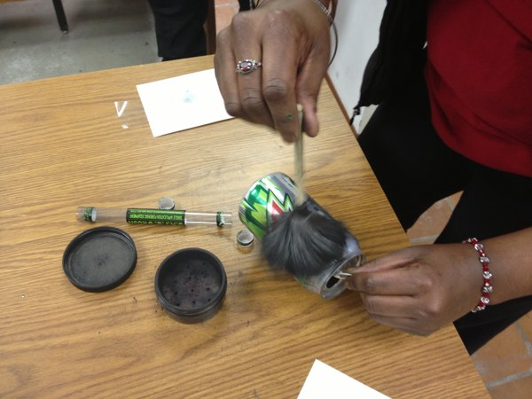 A Citizens' Academy participant brushes black powder onto a soft drink can before using tape to pull a fingerprint from it.
