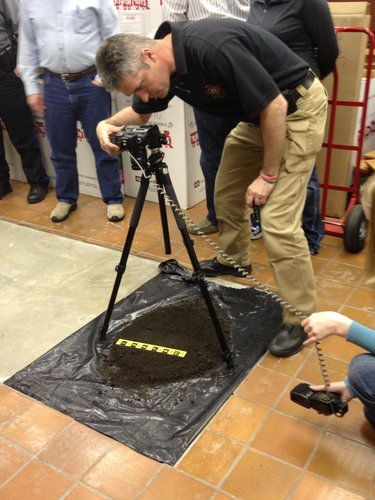 Detective David Axman demonstrates using four angles, a scale, and flash photography to take evidence photos of a shoe print in dirt.