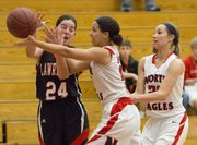 Lawrence High senior Anna Wright (24) loses the ball as she feels double team pressure by Justice Daniel, center, and Danielle Wolfe, right, during Lawrence High's game against Olathe North, held Friday, Feb. 8, 2013 in Olathe.