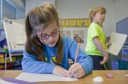 Ava Hertach, a first-grader at St. John school, writes a story during a weekly writing workshop at St. John Catholic School geared toward first-grade aspiring writers. The students write the stories, have them edited and then after having them typed on a computer and printed, they do their own illustrations.