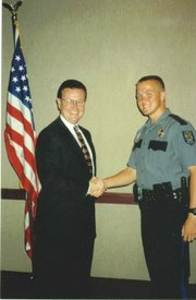 Christopher Mann, as a young police officer with the Lawrence police, shaking hands with former Lawrence Police Chief Ron Olin, left.