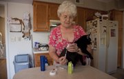 Betty McKinley, Lawrence, gives her cat Midnight her morning insulin shot. Midnight, who is diabetic, gets a shot twice every day.