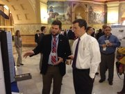 KU's Hunter Harlow shows his research on rock formations in the Ogallala aquifer to Gov. Sam Brownback on Thursday.