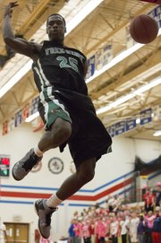 Free State junior Khadre Lane lands after slamming home a dunk during Free State's game against Olathe North, Friday, Feb. 15, 2013 in Olathe.