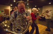 "Paul Jolley, Osawatomie, plays ""When the Saints Go Marching In"" on his French horn while circling the dance floor with other members of the Junkyard Jazz band on Thursday, Feb. 14, 2013, at the American Legion."