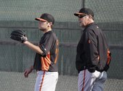 San Francisco Giants manager Bruce Bochy, right, watches as his son, Brett Bochy, throws during a spring training baseball workout on Wednesday, Feb. 13, 2013, in Scottsdale, Ariz.