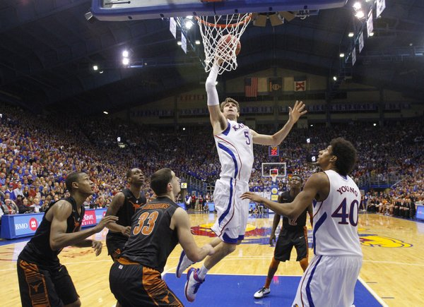 Kansas center Jeff Withey soars in for a dunk over the Texas defense during the second half on Saturday, Feb. 16, 2013 at Allen Fieldhouse.