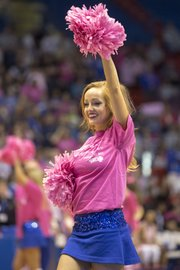 A Kansas cheerleader wears a pink shirt and waves pink pom poms during Kansas&#39; annual &quot;Jayhawks for a Cure&quot; cancer awareness game against Oklahoma, Sunday, Feb. 17, 2013 at Allen Fieldhouse. 