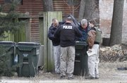 Lawrence police officers remove items from a trash container in an alley in the 700 block between Illinois St. and Mississippi St. after responding to a reported bank robbery at Midwest Regional Credit Union, 1015 W. 6th St., about 12:15 p.m. Wednesday..According to scanner traffic, police are seeking a white male who was last seen on a bicycle, wearing a ski mask and carrying a multicolored backpack with a Kansas Jayhawk logo. An employee at the bank told police that she saw a dye pack that the robber carried away with the money explode in the bag..