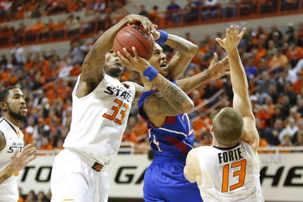 Kansas guard Travis Releford is fouled by Oklahoma State guard Marcus Smart during the first half on Wednesday, Feb. 20, 2013 at Gallagher-Iba Arena in Stillwater, Oklahoma. In front is OSU guard Phil Forte.