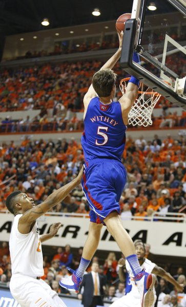 Kansas center Jeff Withey comes in for an alley-opp dunk over Oklahoma State forward Le'Bryan Nash during the first half on Wednesday, Feb. 20, 2013 at Gallagher-Iba Arena in Stillwater, Oklahoma.