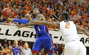 Kansas guard Naadir Tharpe scoops in a shot past Oklahoma State forward Le'Bryan Nash during the second half on Wednesday, Feb. 20, 2013 at Gallagher-Iba Arena in Stillwater, Oklahoma.