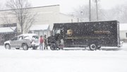A UPS truck gets pulled out of the snow after getting stuck along 9th Street near Mississippi St. Thursday morning. Several inches of snow had fallen on Lawrence well before noon.