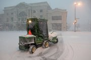 A city worker plows snow in downtown Lawrence early this morning.