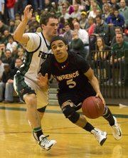 Lawrence High's Justin Roberts (5) drives past Free State's Blake Winslow during their game Friday night at Free State.