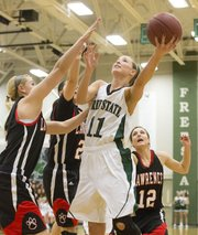 Free State&#39;s Kennedy Kirkpatrick (11) gets around a Lawrence High triple team consisting of Bri Anderson, left, Anna Wright, center, and Emma Kelly (12) for a basket during Free State&#39;s game against Lawrence High Friday night at Free State.
