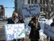 Protestors carry signs Saturday against legislation aimed at teachers.