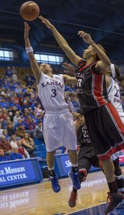 Kansas senior guard Angel Goodrich (3) tries to float a shot over the outstretched arm of Shauntal Nobles during Kansas' women's game against Texas Tech, Sunday at Allen Fieldhouse.