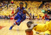 Kansas guard Elijah Johnson looks to grab a steal from Iowa State player Bubu Palo during the first half on Monday, Feb. 25, 2013 at Hilton Coliseum in Ames, Iowa.