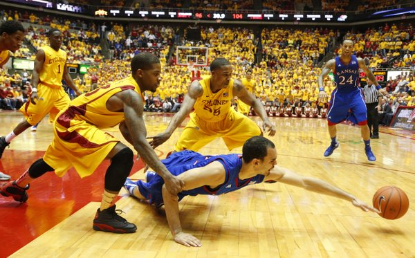 Kansas forward Perry Ellis dives for a loose ball with Iowa State defenders Korie Lucious, front, and Tyrus McGee during overtime on Monday, Feb. 25, 2013 at Hilton Coliseum in Ames, Iowa.