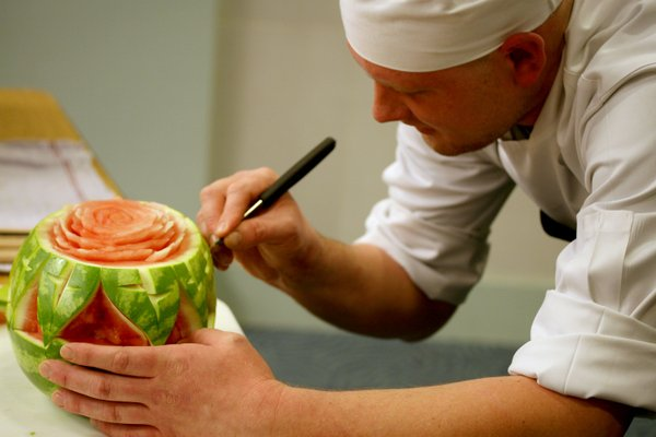 Mike Davis, sous chef for Lawrence's Oread Hotel, carves a watermelon during the 2012 Edible Book Festival at the Shawnee County Public Library in Topeka. Contributed photo.