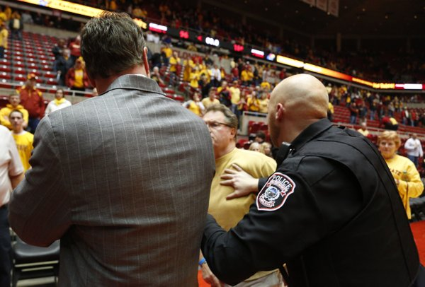 An Iowa State fan is restrained by police after charging at Kansas head coach Bill Self after the Jayhawks' 108-96 overtime win on Monday, Feb. 25, 2013 at Hilton Coliseum in Ames, Iowa.