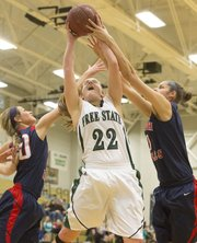 Free State junior Scout Wiebe (22) fights off Olathe North's Danielle Wolfe, left, and Jessica Sheble, right, for a rebound during Free State's first round 6A sub-state game against Olathe North Thursday evening at FSHS. The Firebirds advanced with a 57-44 win.