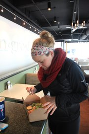 After ordering a salad at Ingredient, 947 Massachusetts St., Kansas University senior Ali Bongard, 21, checks it out before headed home. Ben Sathoff, assistant director of fitness at the KU's Recreation Services, recommends requesting a to-go box at the start of the meal and immediately dividing your plate in half to avoid overeating at restaurants.