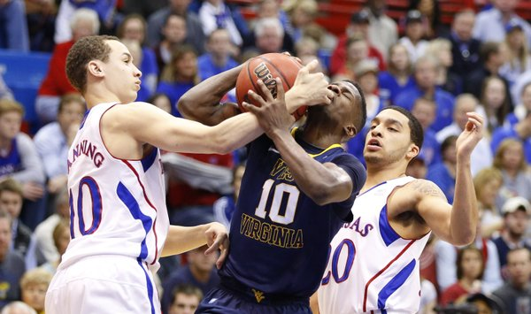 Kansas guard Evan Manning fouls West Virginia guard Eron Harris on the drive during the second half on Saturday, March 2, 2013 at Allen Fieldhouse. At right is KU guard Niko Roberts.