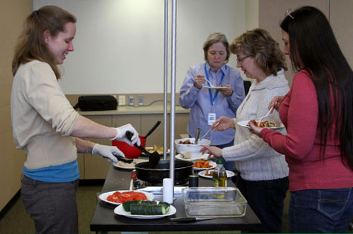 Karla Wessling, dietetic intern, serves up dishes containing functional foods to Health Department staff members.