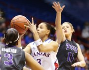 Kansas guard Angel Goodrich ducks between Texas Christian defenders Veja Hamilton (3) and Kamy Cole (11) for a bucket during the first half, Tuesday, March 5, 2013 at Allen Fieldhouse.