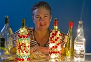 Julie Miller displays some of her crafted wine bottle night lights. Miller and her friend Bonnie Jackson, both of Lawrence, will sell their items at the Spring Arts and Crafts Festival Saturday at the Douglas County Fairgrounds.