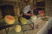 Mike Davis, Sous Chef at the Oread Hotel, demonstrates how to carve fruit March 7 at the hotel. Davis usually carves flowers into honeydew, cantaloupe and watermelon, but he can create different designs on most fruits or vegetables. BELOW: Davis shows off a carved watermelon.