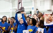 Surrounded by her Kansas University teammates, senior Andrea Geubelle hoists the second-place team trophy at the NCAA Indoor Track and Field Championships on Saturday, March 9, 2013, in Fayetteville, Ark. Geubelle won the long-jump and triple-jump individual titles, and KU placed second for the second-straight season.