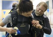 Scuba Shack owner Dave Bach, right, helps Kaiti Smith, Lawrence, adjust her oxygen tank vest at the Lawrence Indoor Aquatic Center, Wednesday, March 13, 2013.