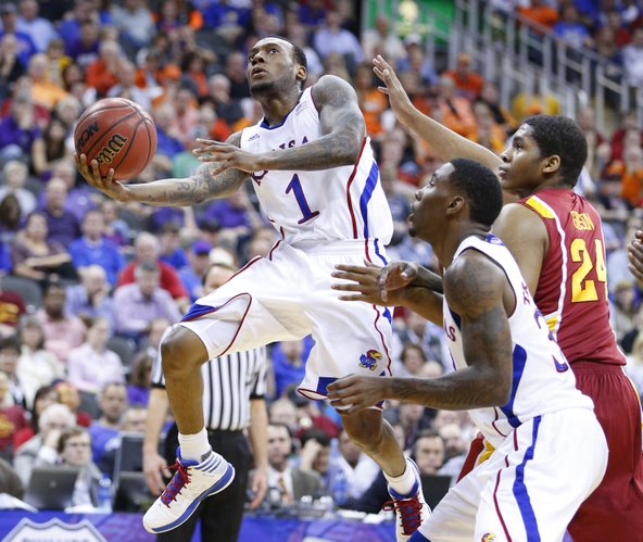 Kansas guard Naadir Tharpe hangs for a shot past Iowa State center Percy Gibson and teammate Jamari Traylor during the first half of the semifinal round of the Big 12 tournament on Friday, March 15, 2013 at the Sprint Center in Kansas City, Missouri.