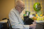 Frank Carlson, 87, a resident at Brandon Woods at Alvamar, hugs Patrick, the nursing home's resident cat. Patrick will have a party in his honor today to celebrate his first birthday.