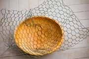 Use a bowl to help shape the chicken wire base for the nest. Soften twigs in water to make them pliable.