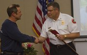 Lawrence-Douglas County Fire Medical Chief Mark Bradford hands retired Capt. Allen Johnson a fire axe for his years service Tuesday during a reception at the department's offices at 1911 Stewart Ave. Johnson joined the department in 1977, and was its most senior member.