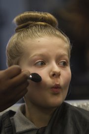Evie Parker, 9, puckers for her makeup application Wednesday at the Lawrence campus of Marinello Schools of Beauty at the Day of Beauty for young ladies from the Boys and Girls Club of Lawrence.
