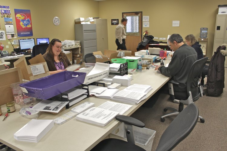 Workers at the state&#39;s Medicaid eligibility clearinghouse shown at the sorting tables where mailed and paper application forms are processed and then scanned for entry to the state&#39;s computerized enrollment and eligibility system. The front end of the new KEES system is already being used for some sign-ups, foregoing the need for the paper shuffling.