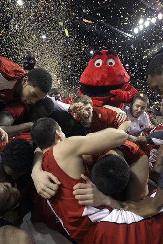 Western Kentucky basketball players fall to the floor by the team's mascot after winning the Sun Belt Conference championship  game on March 11. (AP Photo/Danny Johnston)