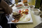 A cook at Genovese pipes whipped cream on top of carrot bread French toast. The dish, served with eggs and bacon, was a recent breakfast special at the restaurant.