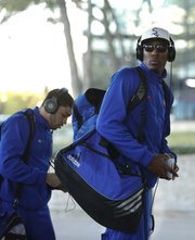 Kansas players Jamari Traylor, right, and Niko Roberts exit the team bus as they arrive at the Hyatt Regency Dallas on Wednesday, March 27, 2013.