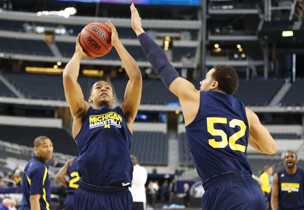 Michigan guard Trey Burke heads up to the bucket against forward Jordan Morgan during a day of practices and press conference for teams in the South Regional at Cowboys Stadium in Arlington, Texas