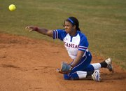 Kansas junior second baseman Ashley Newman makes a throw to first from her knees after making a diving play on the ball during Kansas' softball game against Texas, Thursday, March 28, 2013 at Arrocha Ballpark.