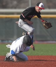 Lawrence High second baseman CJ Stuever, top, avoids Olathe Northwest's Austin Hansen after making a force out on Thursday, March 28, 2013, at LHS.
